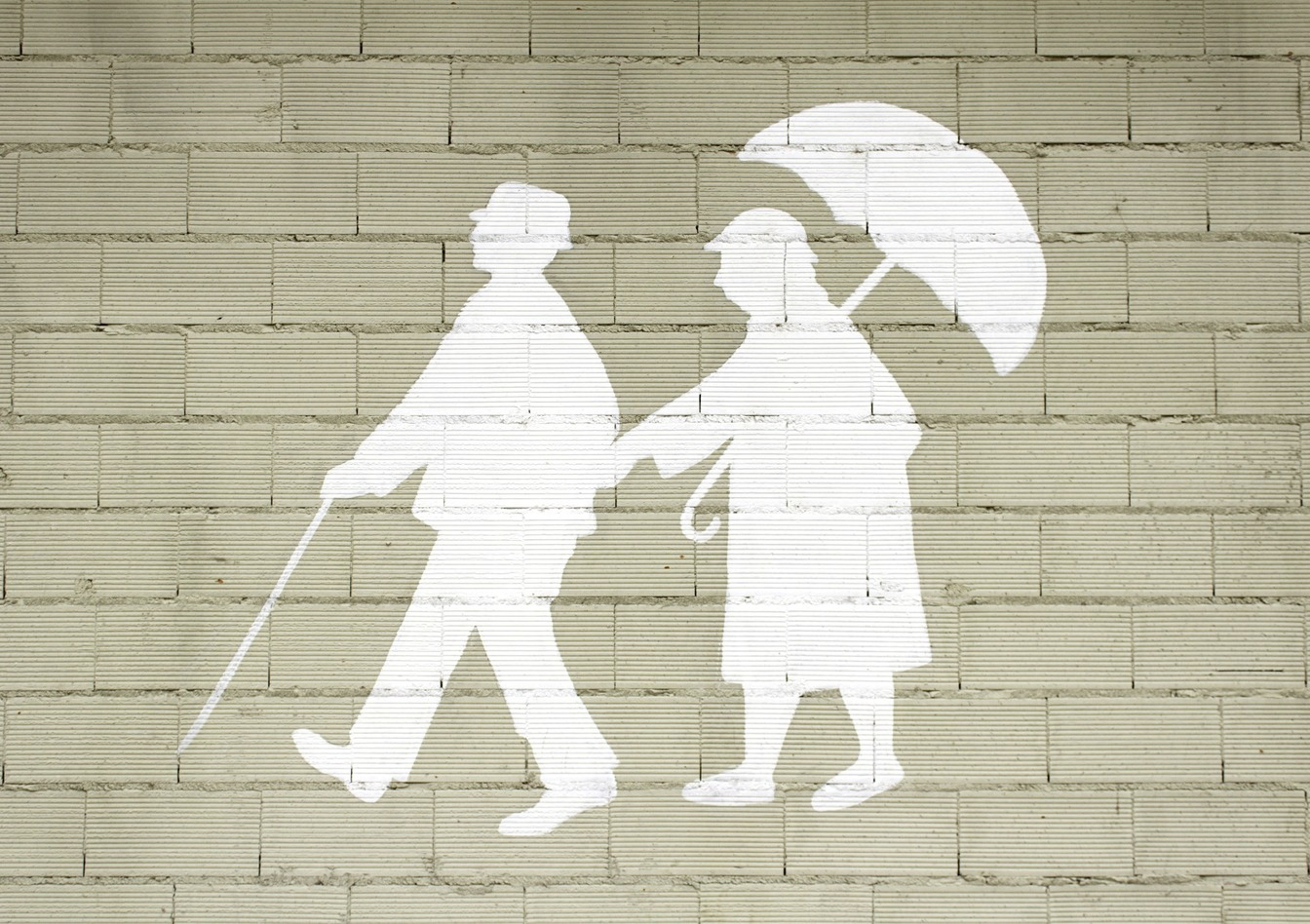 A white painted silhouette of an older man with a walking stick and an older woman with an umbrella holding hands