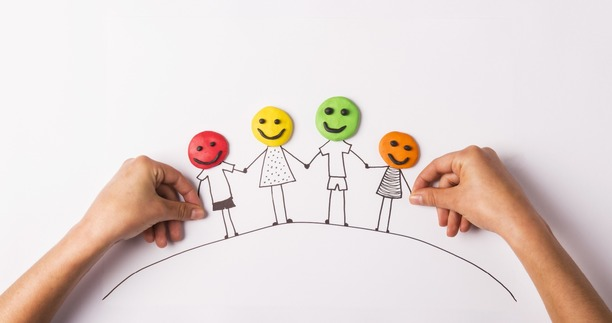 A family drawn in black pen, with play-doh faces in different colours, holding hands.