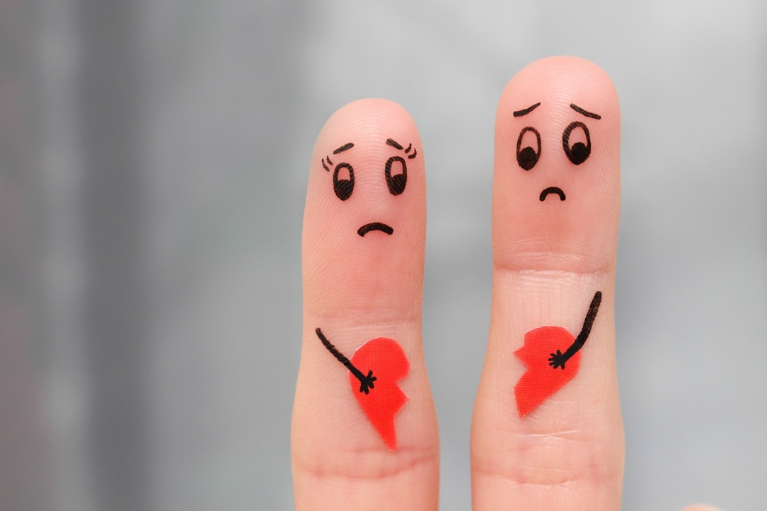 Two fingers with sad faces drawn on, each holding half of a broken heart.