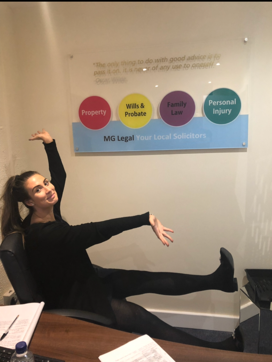 Our Chloe Cardwell sitting in our Garstang office, showing off our wall plaques with inspirational quotes.