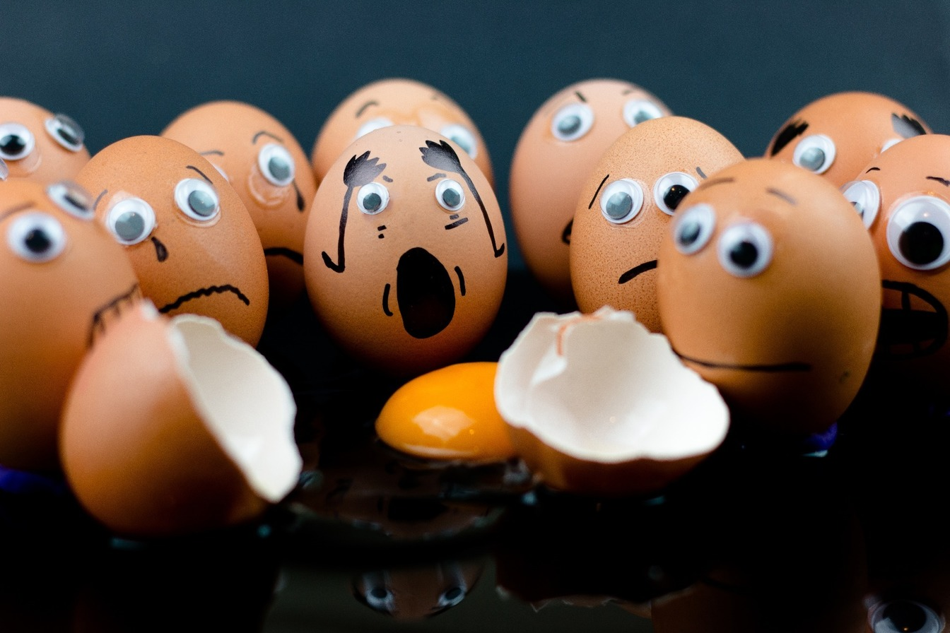 A cracked egg, surrounded by eggs with worried faces