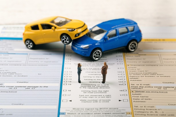 A toy yellow and blue car on top of an insurance form.