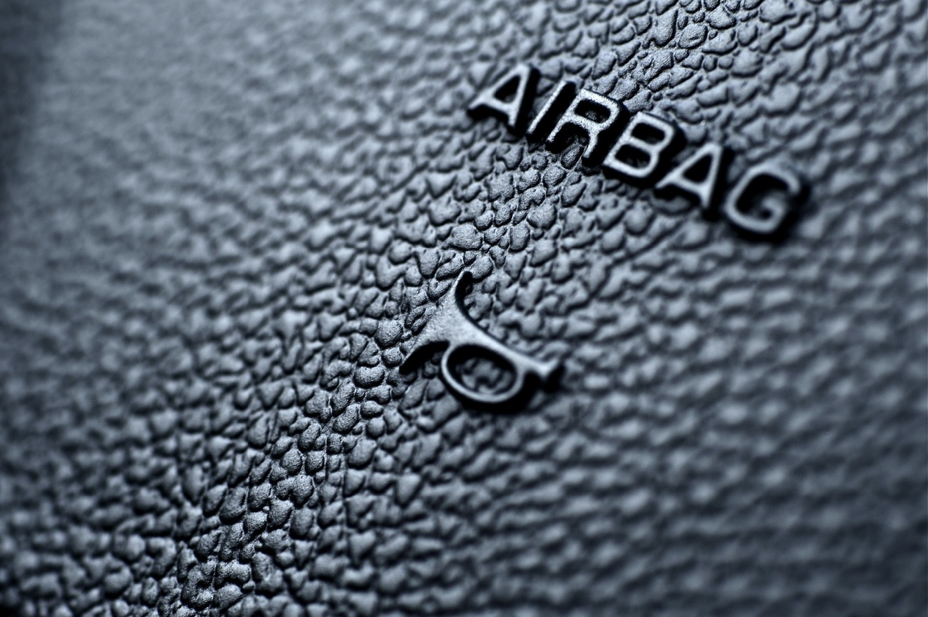 An airbag symbol in a car in black.