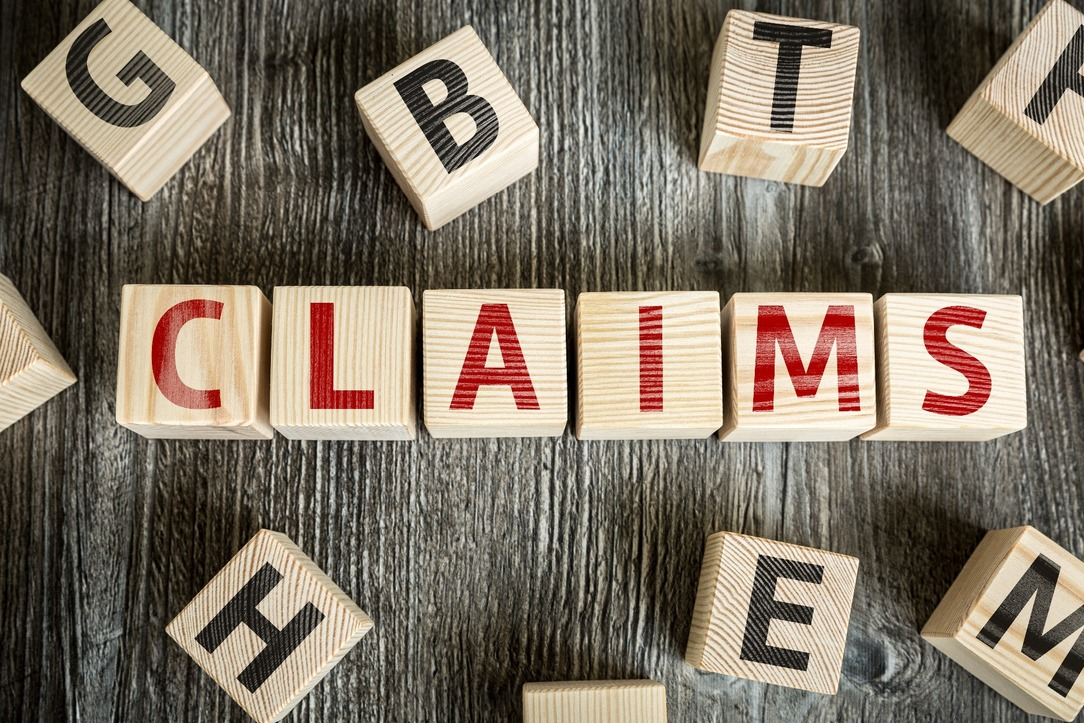 'CLAIMS' spelled out in wooden blocks, in red writing.