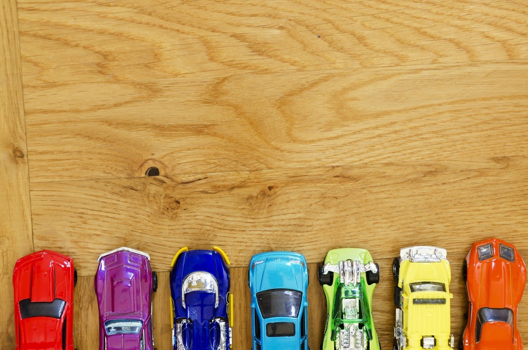 A line of different coloured toy cars, in order of red, purple, dark blue, light blue, green, yellow and orange.