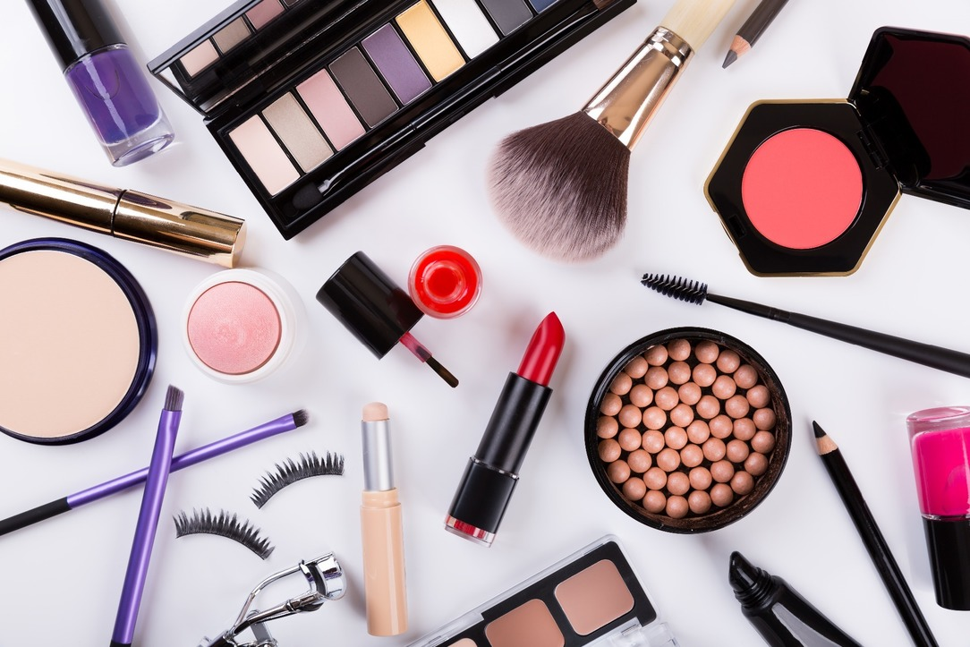 An array of beauty products, such as mascara, eyeliner, eyeshadow, blush, foundation and eyelashes.