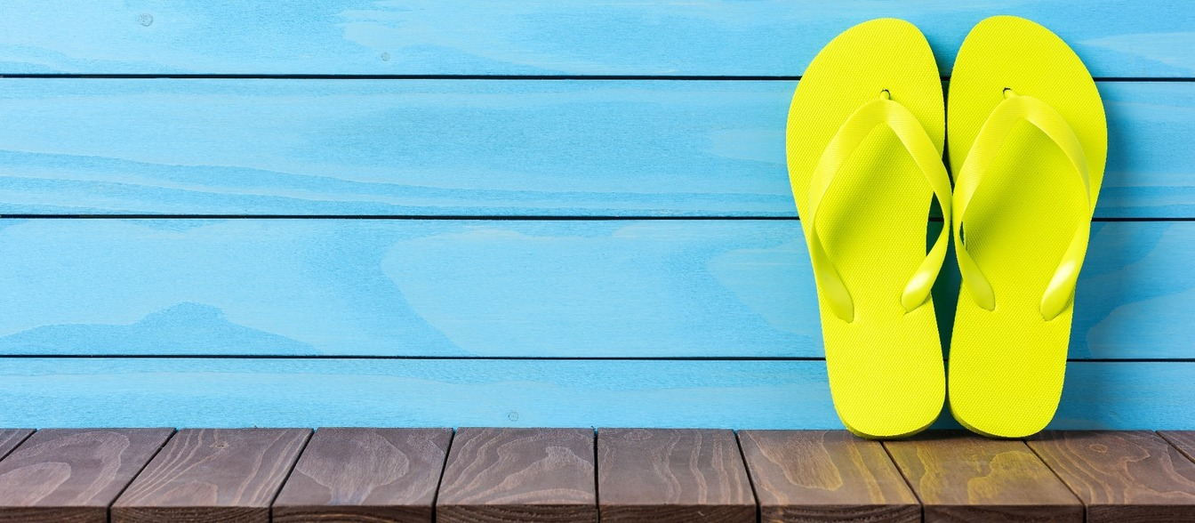 A yellow pair of flip flops, propped against a blue, wooden wall.