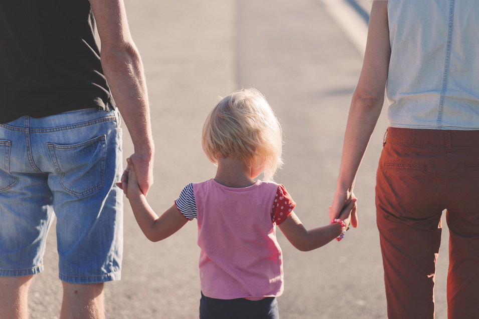 A child wearing a pink top, holding a hand of either parent on a sunny day.