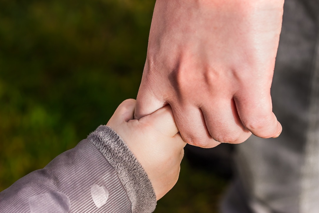 A small child, holding their parent's hand.