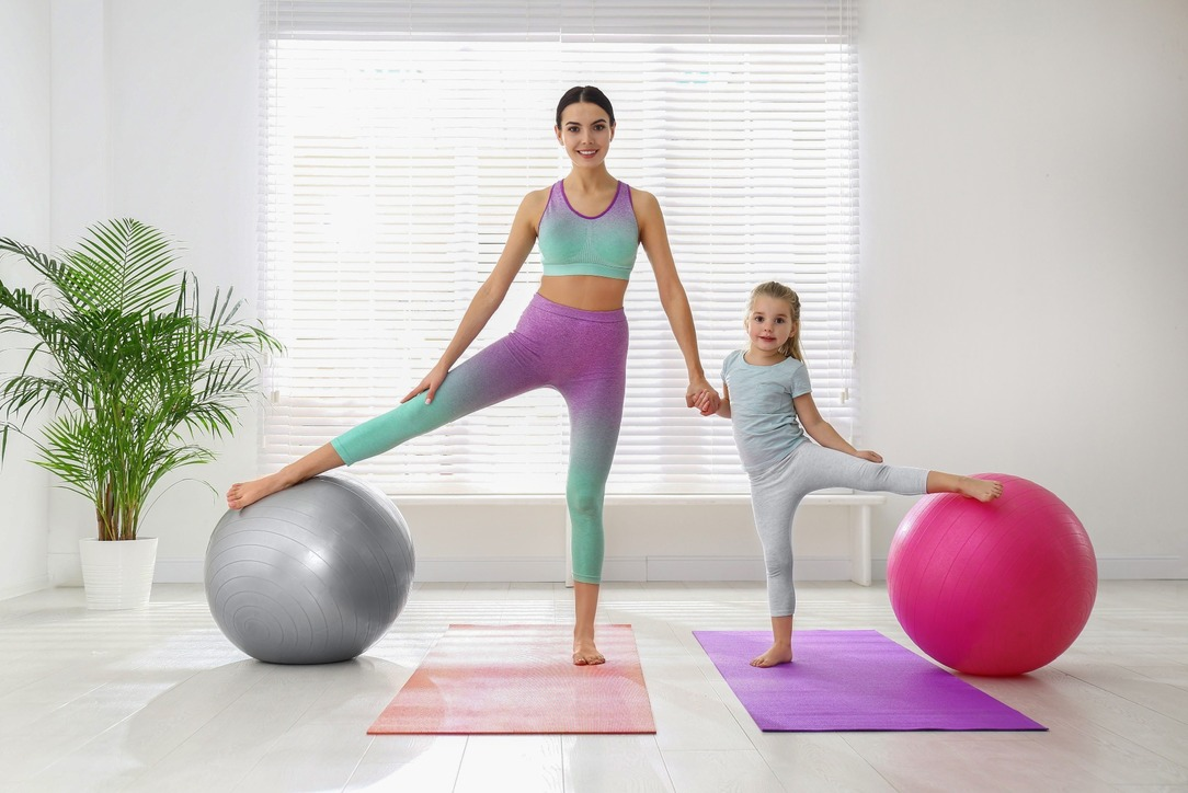 A woman and a young girl exercising with yoga mats and large exercise balls inside a house.