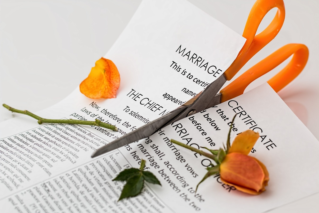 A pair of orange scissors being used to cut up a marriage certificate, and orange roses.