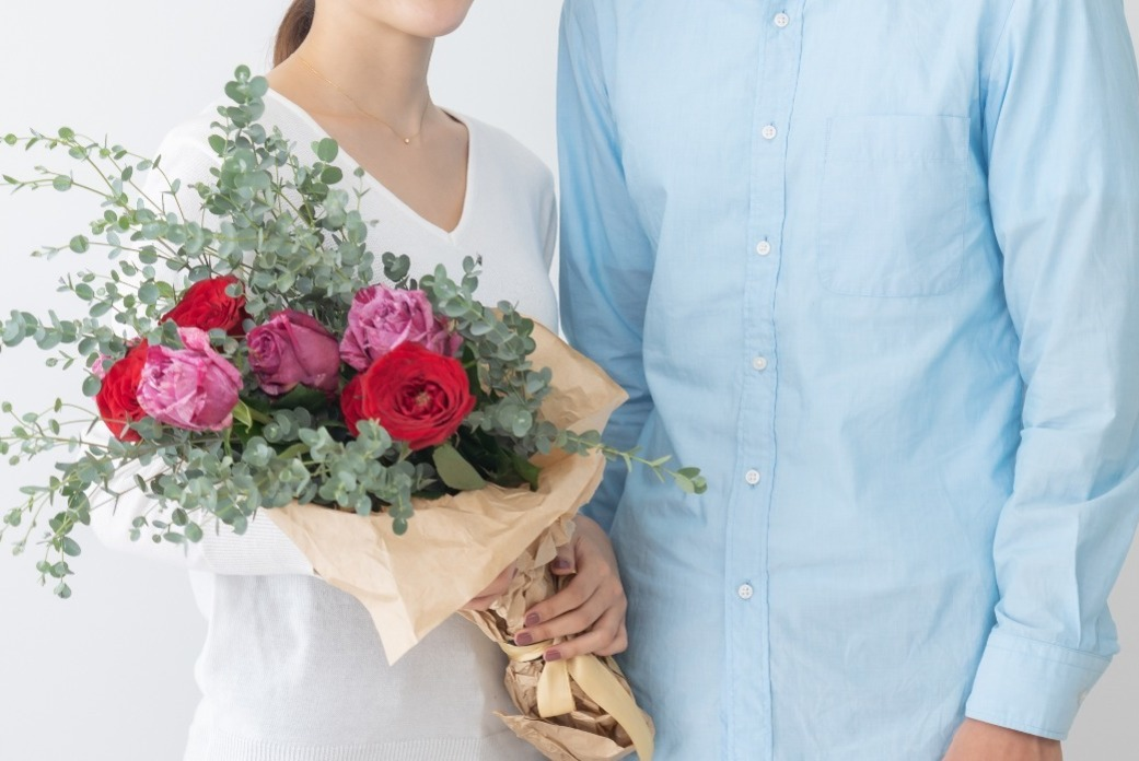 A couple holding a bouquet of flowers.