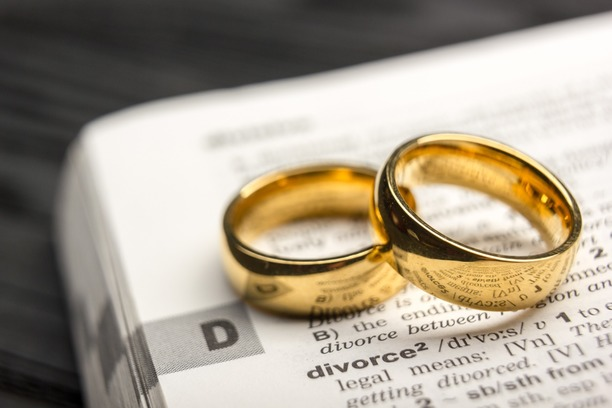 Wedding rings resting on the word divorce.