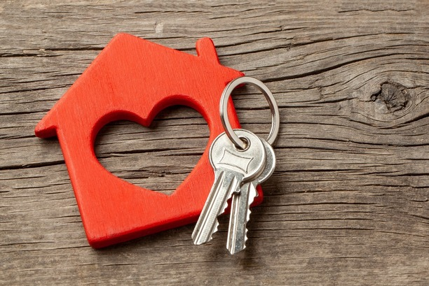 A wooden block of a house with a heart in the middle.  A set of keys rests on top.