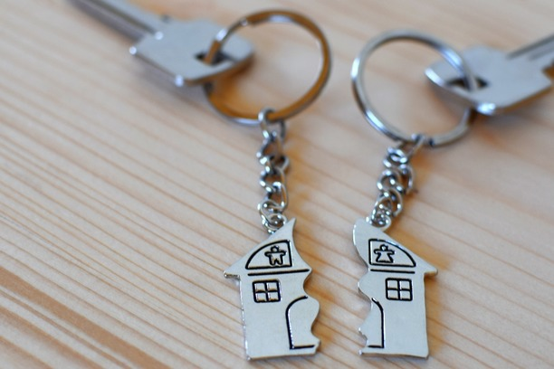 Two keys, each attached to their own keyring showing half of a house.