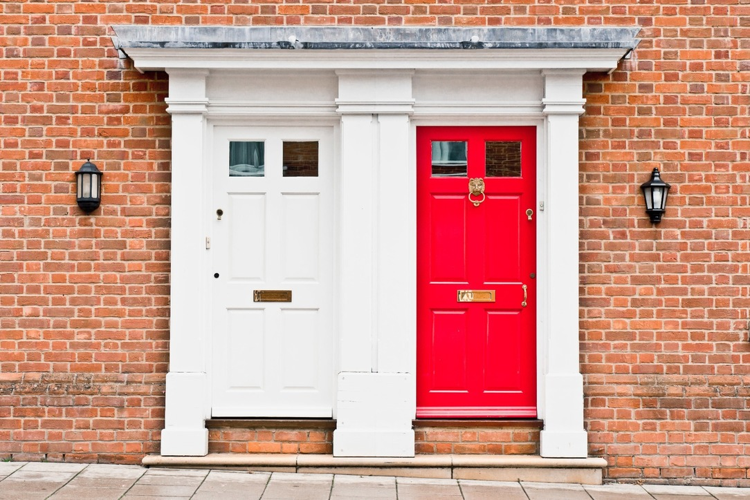 A house with two front doors, one white and one red.