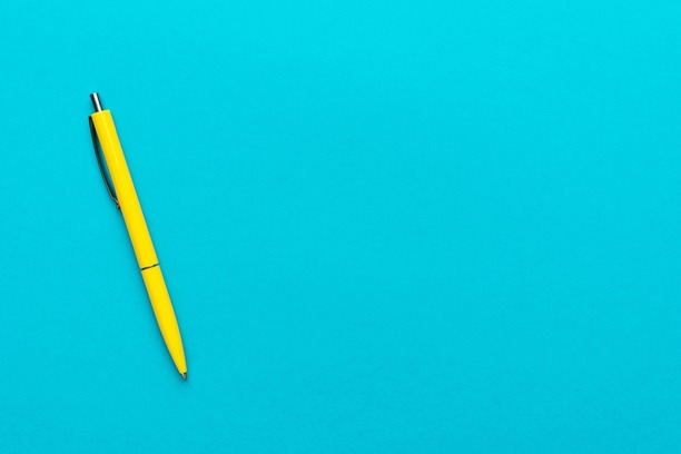 A yellow pen resting on a blue background.