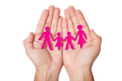A pair of hands holding a pink paper-cut out of a family.