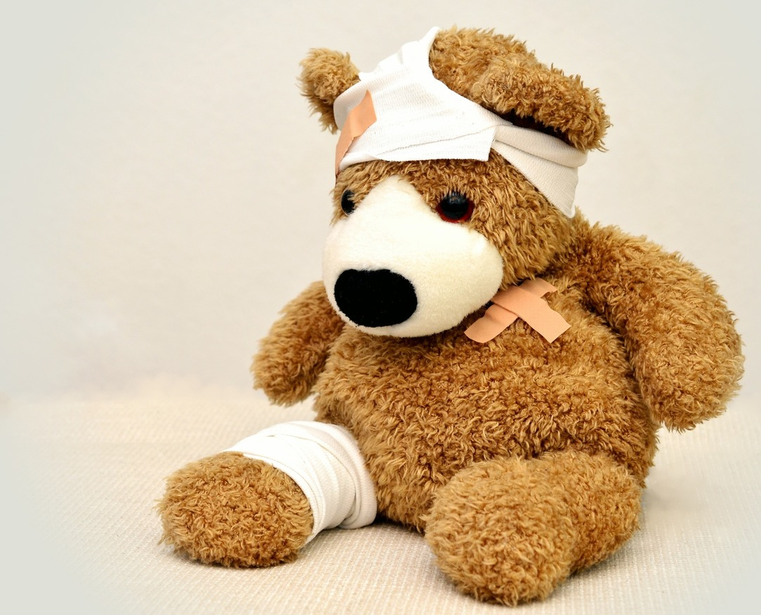 A teddy bear, with a bandage on his leg and head, and a plaster on his torso.