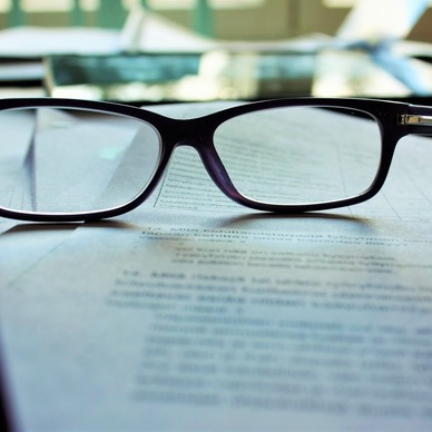 A paid of black-rimmed glasses standing on a piece of paper.