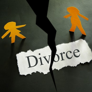 A yellow paper person and an orange paper person standing either side of a crack on the floor, with a ripped piece of paper saying divorce.