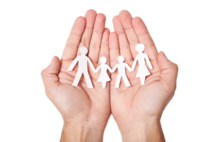 A pair of hands holding a paper cut-out of a family.