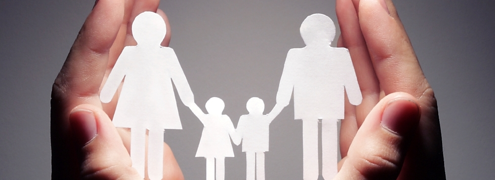 Two hands cradling a paper cut out family