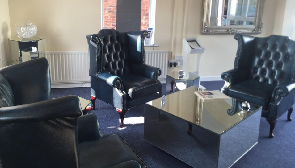 The interior of the Garstang office with blue, leather chairs and mirrored table and side table.