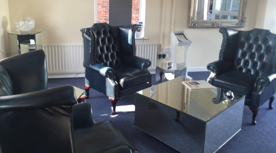The blue, leather chairs and mirrored furniture in our Garstang office reflection.