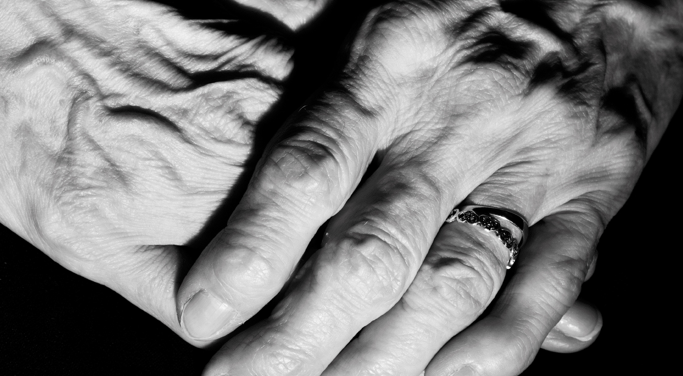 Wrinkled hands closed together.